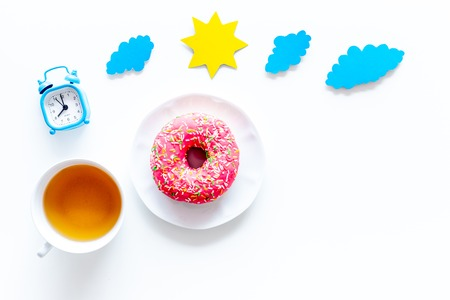 Time for breakfast concept. Tea, donut near alarm clock, sun and clouds cutout on white background top view copy space