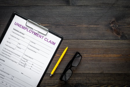 Unemployment claim form on dark wooden background top view copy space Banco de Imagens