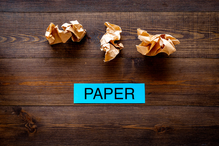 Waste suitable for recycle. Crumpled paper near printed word paper on dark wooden background top view copy space