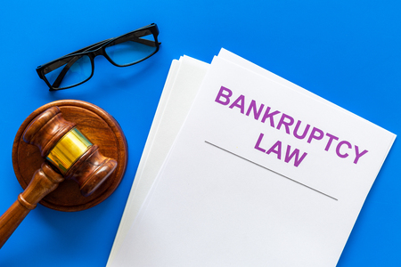 Words bankruptcy law written on the documents near judge gavel on blue background top view