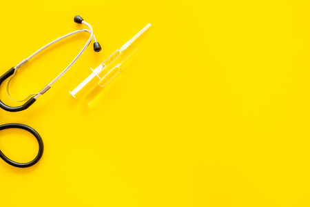 Infuenza, flu vaccine in syringe near stethoscope on yellow background top view.