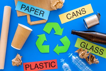グリーンリサイクルエコシンボル近くのリサイクルに適したMatherials。言葉の紙、ガラス、プラスチック、青い背景の上のビューに缶。