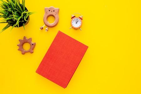 小さな子供のための夜に読書。黄色の背景の上のビューにおもちゃの近くで予約。 写真素材 - 107418165