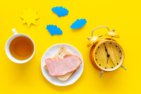 Parts of day. Morning. Time for breakfast. Tea, sandwich near alarm clock, sun and clouds cutout on yellow background top view. Reklamní fotografie