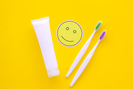Teeth care, dental care. Toothbrushes and tooth paste near smile face emoji on yellow background top view.