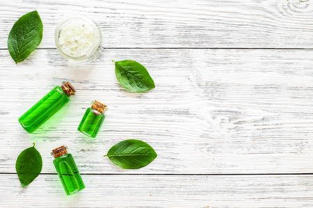 Natural hipoallergenic cosmetics with tea tree essential oil. Oil, lotion, leaves on white wooden background top view.