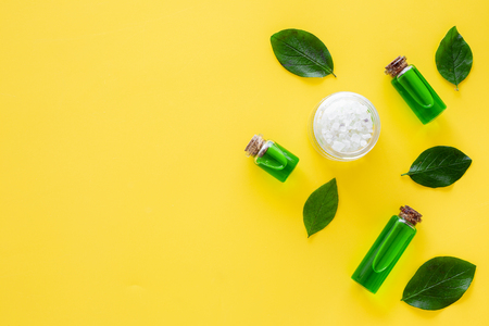 Natural hipoallergenic cosmetics with tea tree essential oil. Oil, lotion, leaves on yellow background top view.
