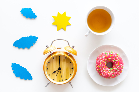 Time for breakfast concept. Tea, donut near alarm clock, sun and clouds cutout on white background top view. Reklamní fotografie