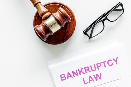 Words bankruptcy law written on the documents near judge gavel on white background top view.