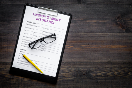 Unemployment insurance form on dark wooden background top view.