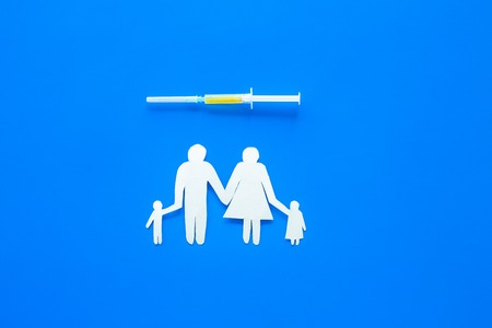 Vaccination for healthy family, vacctination of children. Flu. Syringe near family cutout on blue background top view.