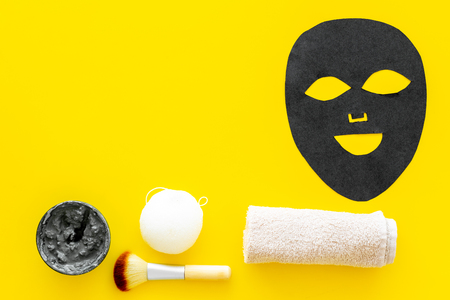 Black facial mask. Black head remover mask. Mask with clay on yellow background top view.