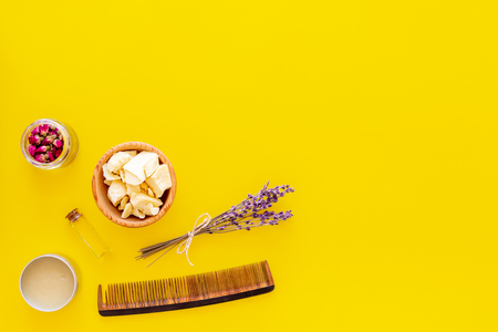 Natural oil for hair. Jojoba, argan, coconut oil near bunch of lavender and hairbrush on yellow background top view.