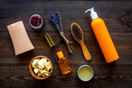 Professional shampoo, balm, conditioner based on jojoba, argan or coconut oil. Bottles and oil on dark wooden background.