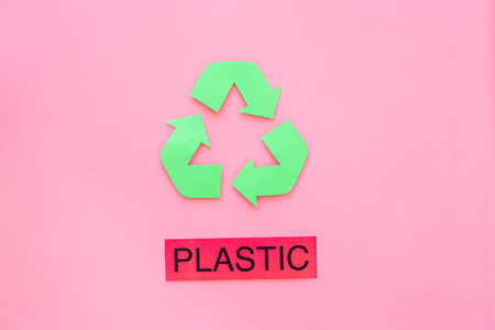 Types of matherial for reycle and reuse. Printed word plastic near eco symbol recycle arrows on pink background top view.