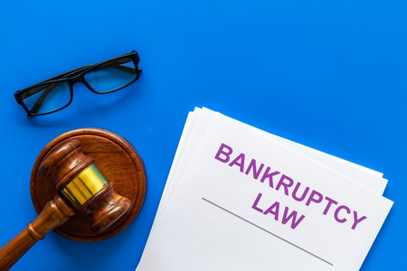 Words bankruptcy law written on the documents near judge gavel on blue background top view copy space
