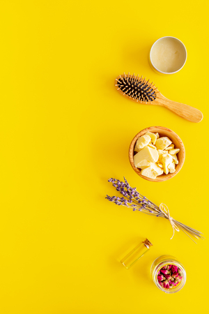 Hair treatment with natural products. Jojoba, argan, coconut oil near bunch of lavender and hairbrush on yellow background top view.