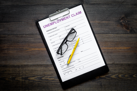Unemployment claim form on dark wooden background top view.