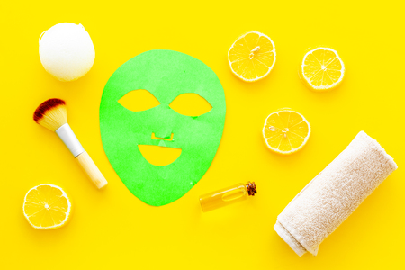 Face spa products. Facial mask, cream, oil near lemon slices and towel on yellow background top view