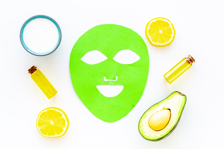 Cosmetics with natural ingredients. Facial mask, cream and lotion based on avocado and lemon essential oil on white background top view Stock Photo