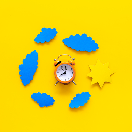 Time of day. Morning. Awakening and sunrise. Sun and clouds cutout near alarm clock on yellow background top view copy space