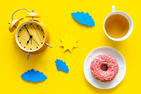 Time for breakfast concept. Tea, donut near alarm clock, sun and clouds cutout on yellow background top view