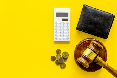 Financial failure, bankruptcy concept. Judge gavel, wallet, coins, calculator on yellow background top view copy space