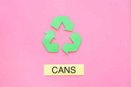 Types of matherial for reycle and reuse. Printed word cans near eco symbol recycle arrows on pink background top view copy space