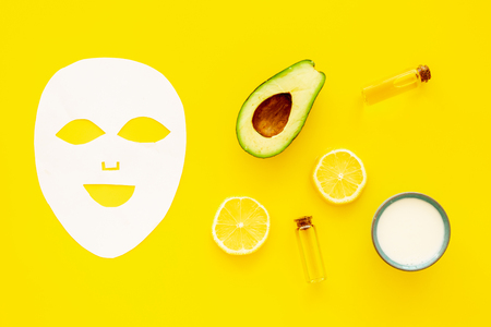 Skin care. Facial mask, cream and lotion near avocado and lemon on yellow background top view.