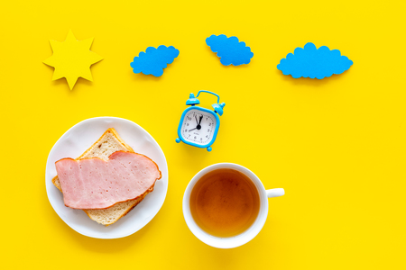Parts of day. Morning. Time for breakfast. Tea, sandwich near alarm clock, sun and clouds cutout on yellow background top view copy space