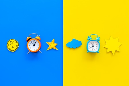 Sleep time, clock on the bed and time to awake concept. Alarm clock near sun, moon, stars cutout on blue and yellow background top view copy space