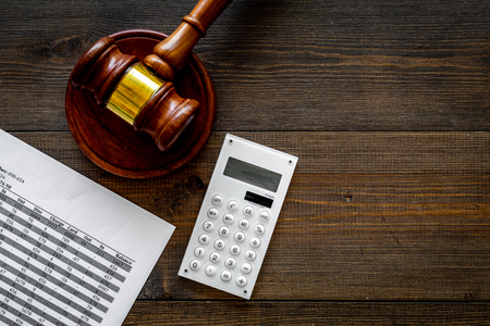 Declare bankruptcy concept. Judge gavel, financial documents, calculator on dark wooden background top view.