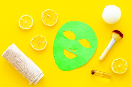 Face spa products. Facial mask, cream, oil near lemon slices and towel on yellow background top view.