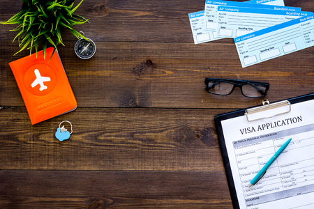 Planning a vacation, planning a trip. Visa application form near passport and airplane ticket on dark wooden background top view.