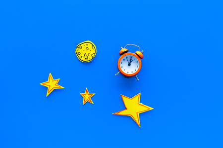 Sleep time, clock on the bed concept. Alarm clock near moon and stars cutout on blue background top view copy space