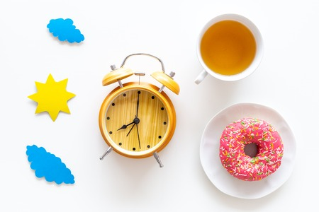 Time for breakfast concept. Tea, donut near alarm clock, sun and clouds cutout on white background top view Reklamní fotografie
