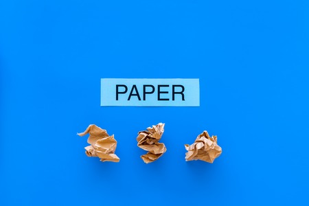 Waste suitable for recycle. Crumpled paper near printed word paper on blue background top view copy space