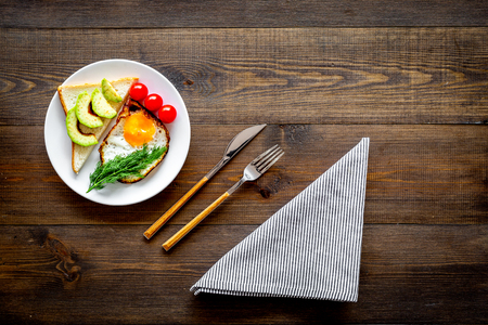 Healthy hearty breakfast. Fried eggs with vegetables near toast with avocado on dark wooden background copy space