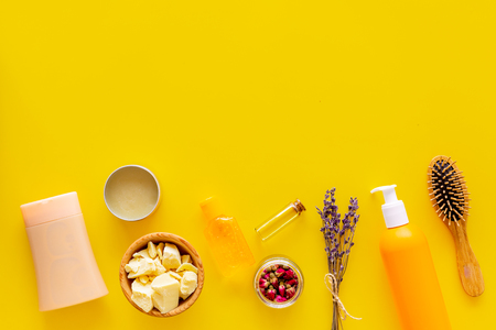 Professional shampoo, balm, conditioner based on jojoba, argan or coconut oil. Bottles and oil on yellow background top view. Stok Fotoğraf