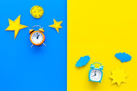 Schlafzeit, Uhr auf dem Bett und Zeit zum Erwachen Konzept. Wecker nahe Sonne, Mond, Sternausschnitt auf Draufsicht des blauen und gelben Hintergrunds.