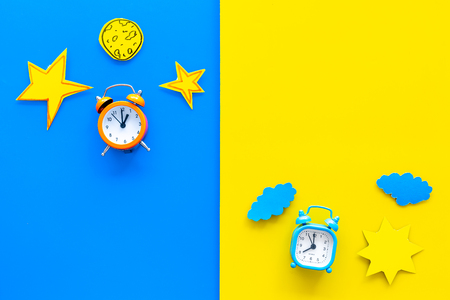 Slaaptijd, klok op het bed en tijd om wakker te worden. Wekker dichtbij zon, maan, sterrenknipsel op blauwe en gele hoogste mening als achtergrond.