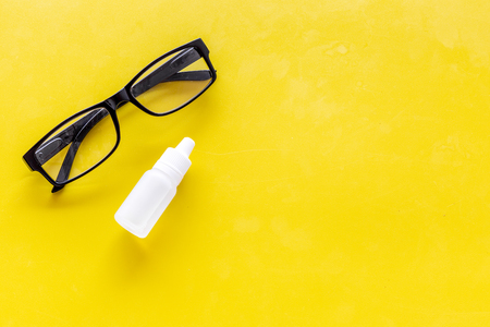Eye health. Glasses with transparent optical lenses and eye drops on yellow background top view.