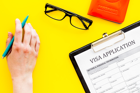 Fill visa application form. Empty blank near passport cover with airplane on yellow background top view.