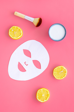 Face spa products. Facial mask, cream, brush near lemon slices on pink background top view.