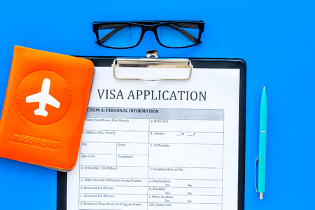 Fill visa application form. Empty blank near passport cover with airplane on blue background top view.