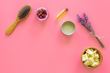 Hair treatment with natural products. Jojoba, argan, coconut oil near lavender and comb on pink background top view. Stock Photo
