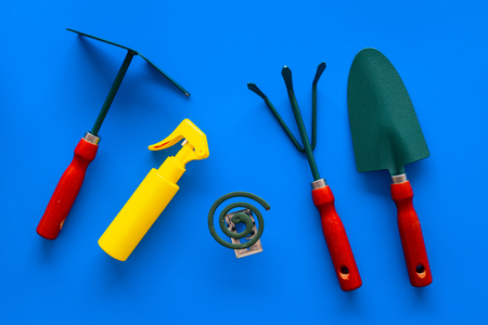 Mosquito protection for garden. Mosquito coil and spray near garden tools on blue background top view. Banque d'images - 108113163