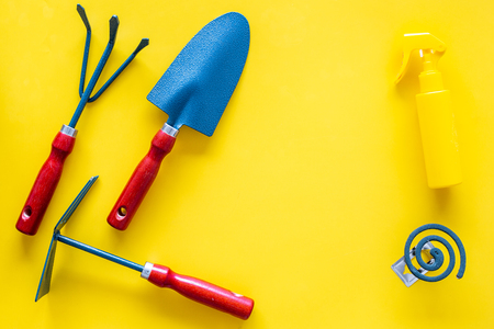 Mosquito protection for garden. Mosquito coil and spray near garden tools on yellow background top view. Banque d'images - 108113647