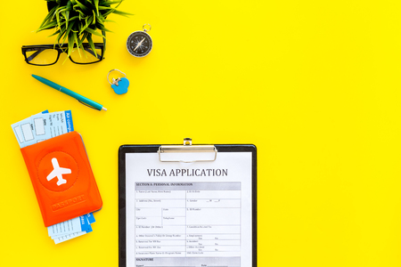Planning a vacation, planning a trip. Visa application form near passport and airplane ticket on yellow background top view.