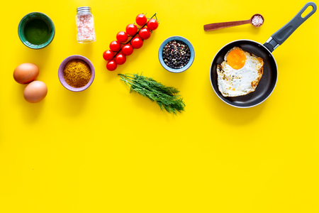 Recipe of fried eggs with vegetables. Ready eggs in a frying pan near cherry tomatoes, greenery, spices, raw eggs on yellow background top view.